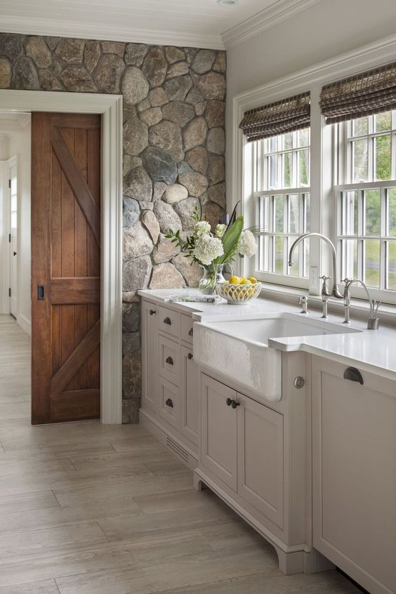 a white farmhouse kitchen with a stone accent wall, woven shades and barn doors that add coziness to it