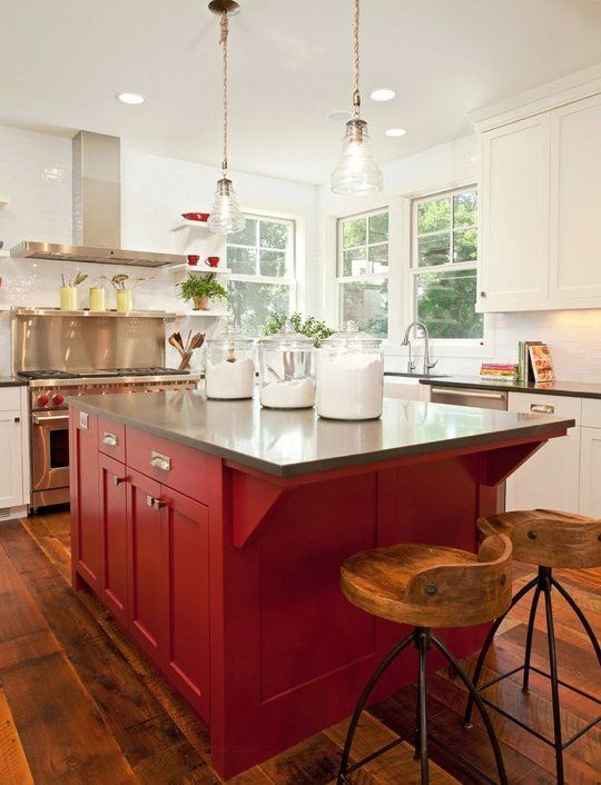 a white kitchen with black stone countertops and a red kitchen island plus vintage pendant lamps is super bold and elegant