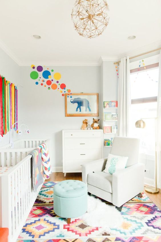 an airy and bright nursery with neutral walls and furniture, colorful textiles, fringe, rugs and some art on the wall