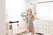 an airy neutral nursery with neutral furniture, a printed rug, a statement plant and neutral textiles is a cozy space