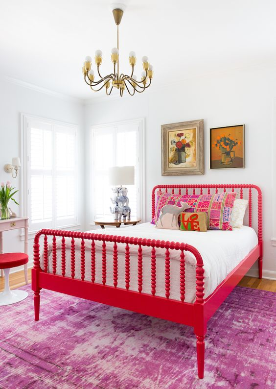 an artistic bedroom with a bold red vintage bed and a stool, chic artworks, a table lamp with elephants and a vintage chandelier