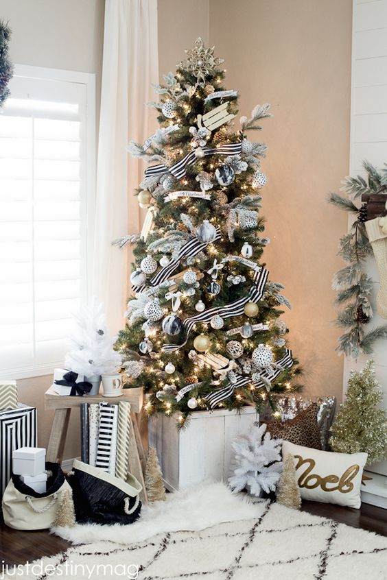an elegant modern Christmas tree with white, silver, black marble and gold ornaments, lights and striped ribbons is very elegant