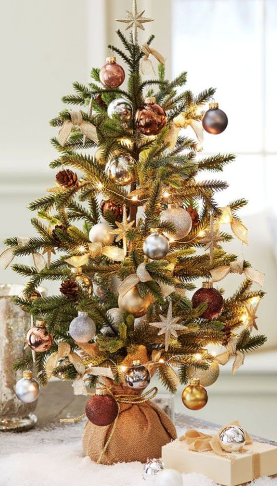 an elegant tabletop Christmas tree with lights, silver, gold and brown ornaments, burlap bows and pinecones