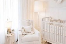 an ethereal neutral nursery with a paneled wall, some vintage furniture, a pendant lamp, white textiles and a tree stump side table