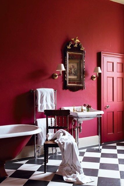 an exquisite red and burgundy bathroom with burgundy walls, a red door, a burgundy bathtub and vintage applainces and furniture