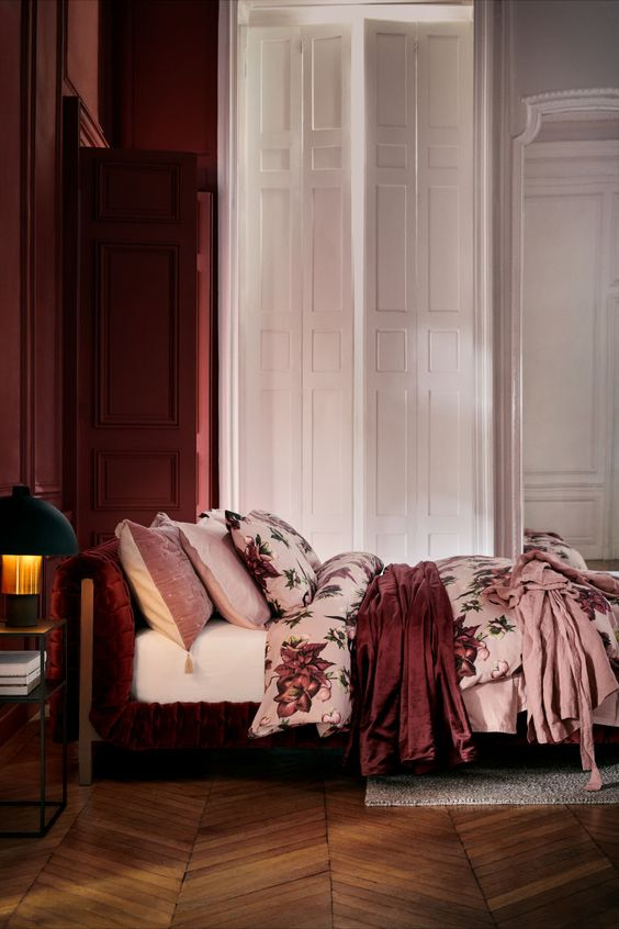 red panels on the walls, a burgundy velvet bed with pink floral bedding and a black nightstand with a chic table lamp