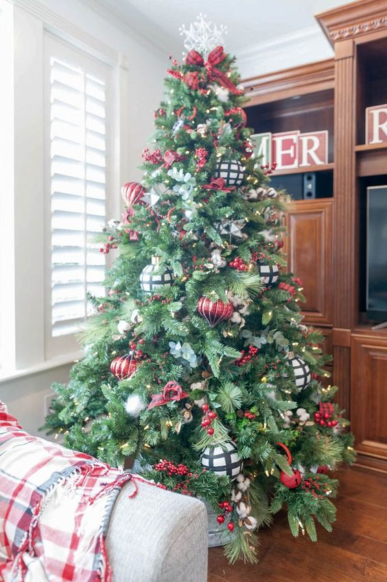a beautiful Christmas tree with lights, red and white plaid ornaments, faux berries and a snowflake on top is a chic and cool idea