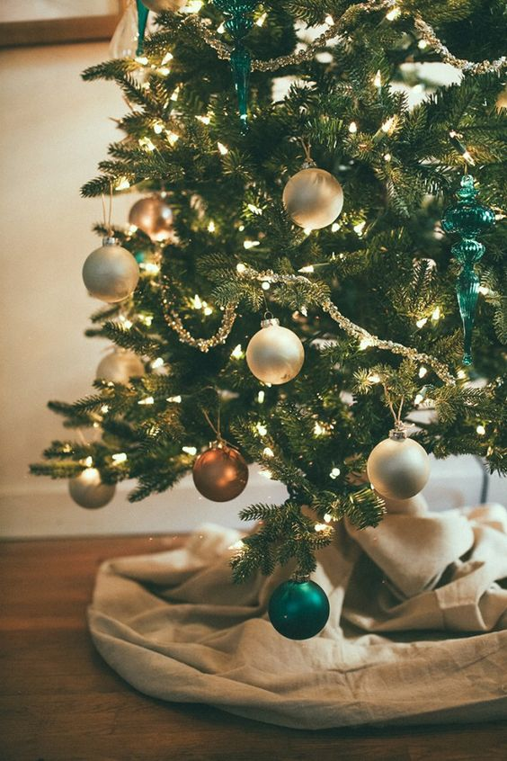 a beautiful Christmas tree with lights, white, copper and emerald ornaments, some burlap to cover the base is a lovely idea