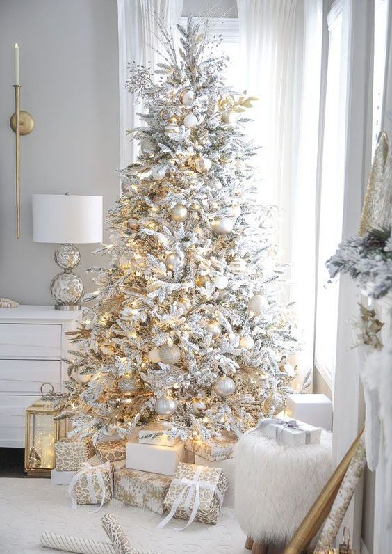 a beautiful flocked Christmas tree with white and metallic ornaments is always a very cool idea for a winter wonderland feel