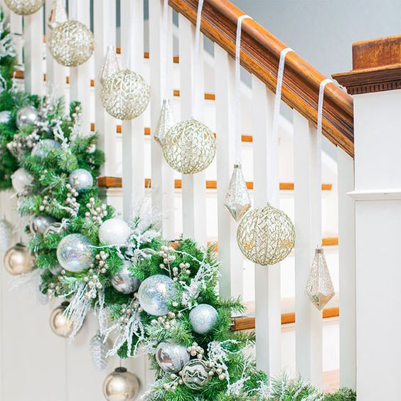 a fir garland with beads, silver and blue ornaments and twigs and gold ornaments for Christmas stairs decor