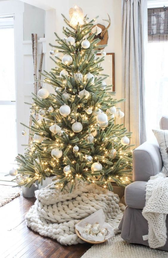 a beautiful Christmas tree with silver and white ornaments, lights and a chunky knit cover is a very cozy and modern piece