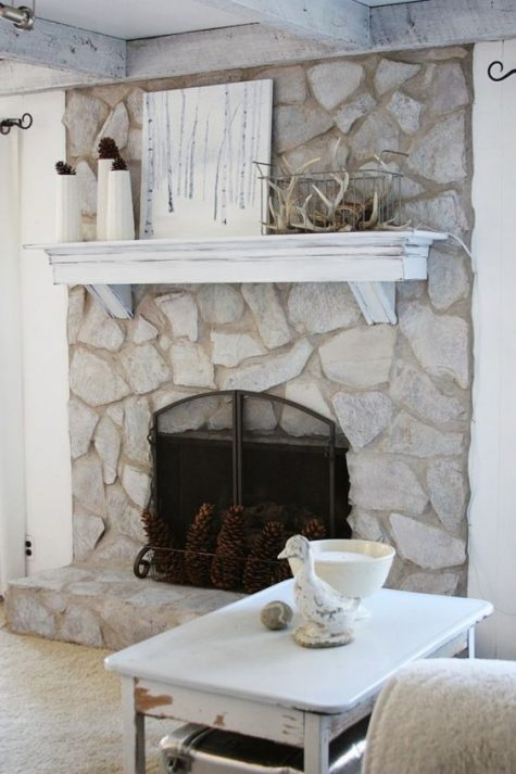 a beautiful whitewashed stone fireplace with pinecones, a whitewashed mantel with antlers and pinecones for a woodland feel
