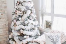 04 a Christmas tree covered with a white faux fur garland, pearly ornaments, a silver topper and lights for a winter wonderland feel