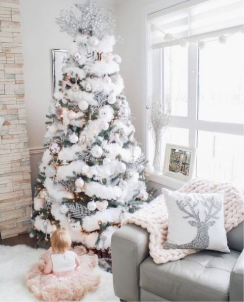 a Christmas tree covered with a white faux fur garland, pearly ornaments, a silver topper and lights for a winter wonderland feel
