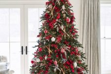 04 a Christmas tree decorated with lights, red berries, branches, plaid ribbons, red and white ornaments is amazing
