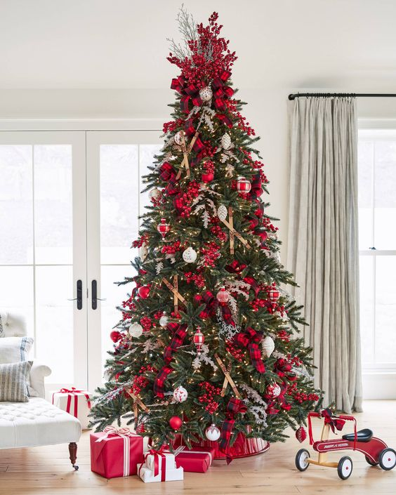 a Christmas tree decorated with lights, red berries, branches, plaid ribbons, red and white ornaments is amazing