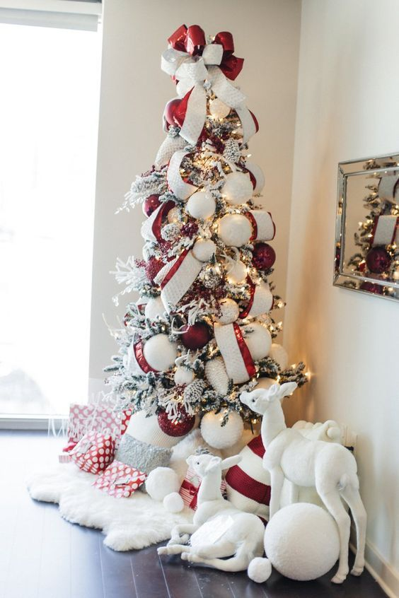 a bold Christmas tree with lights, striped ribbons, red and white ornaments, faux fur and pillows under the tree and some toys