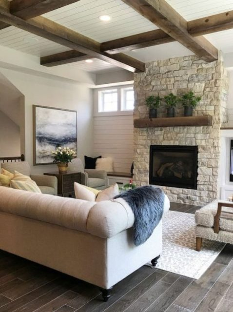 a chic farmhouse living room with a whitewashed stone fireplace and a matching mantel plus wooden beams on the ceiling for more coziness