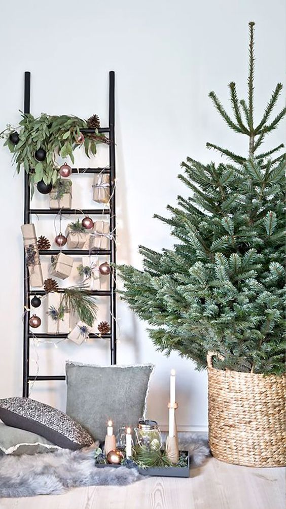 a ladder decorated with pinecones, greenery, copper and black ornaments and gifts attached to it is a modern decoration