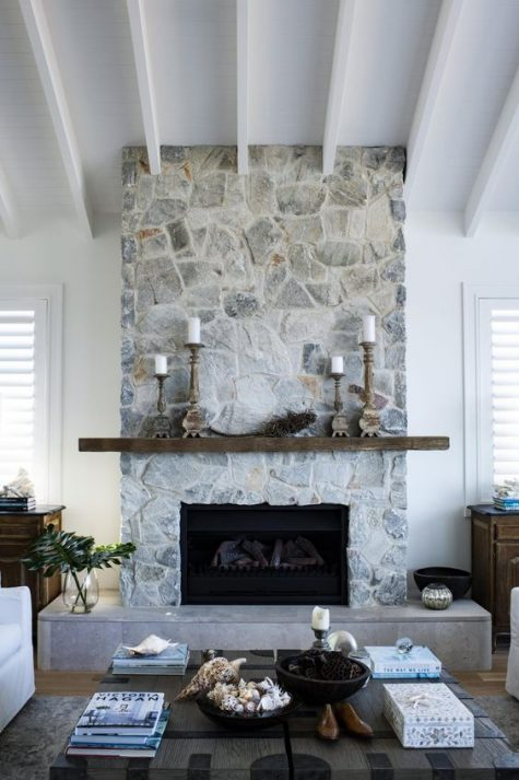 a chic whitewashed stone fireplace with a wooden mantel and grey tiles at the bottom, candles in wooden candleholders