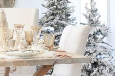 05 a duo of flocked Christmas trees in baskets with faux fur, some faux fur on the table, metallic glasses create a winter wonderland look
