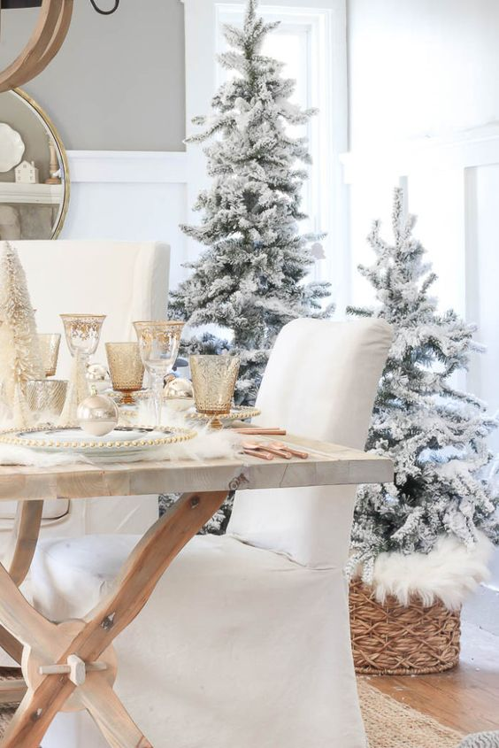 a duo of flocked Christmas trees in baskets with faux fur, some faux fur on the table, metallic glasses create a winter wonderland look