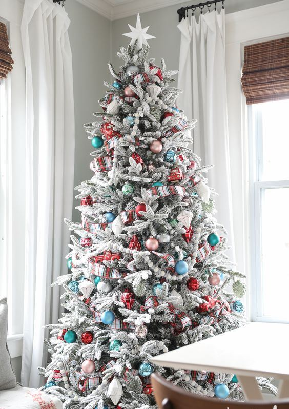 a flocked Christmas tree with green, blue, red and pink ornaments, felt bead garlands and plaid ribbons