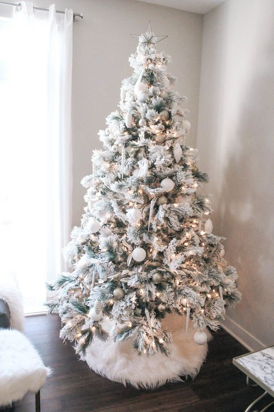 a flocked Christmas tree with lights, silver and white ornaments and icicles and a white faux fur cover for more coziness