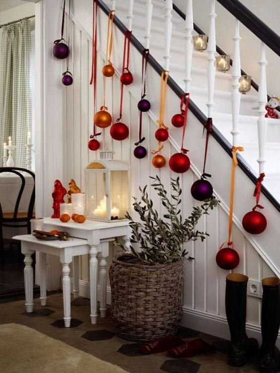 Christmas stairs decor with bold oversized ornaments on ribbons is fun, bright and very cool