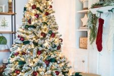 06 a flocked Christmas tree with lights, red and green ornaments and green ribbons is a very cute and chic idea