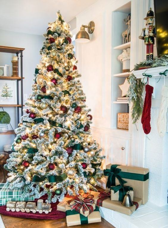 a flocked Christmas tree with lights, red and green ornaments and green ribbons is a very cute and chic idea