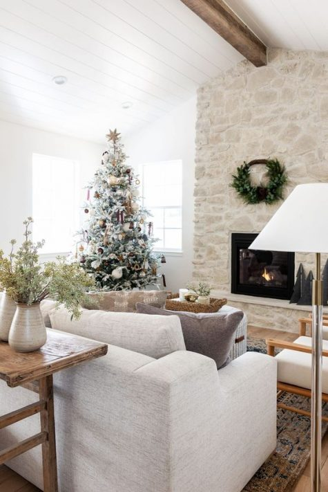 a gorgeous whitewashed stone fireplace with a wreath over it takes over the whole space and looks chic