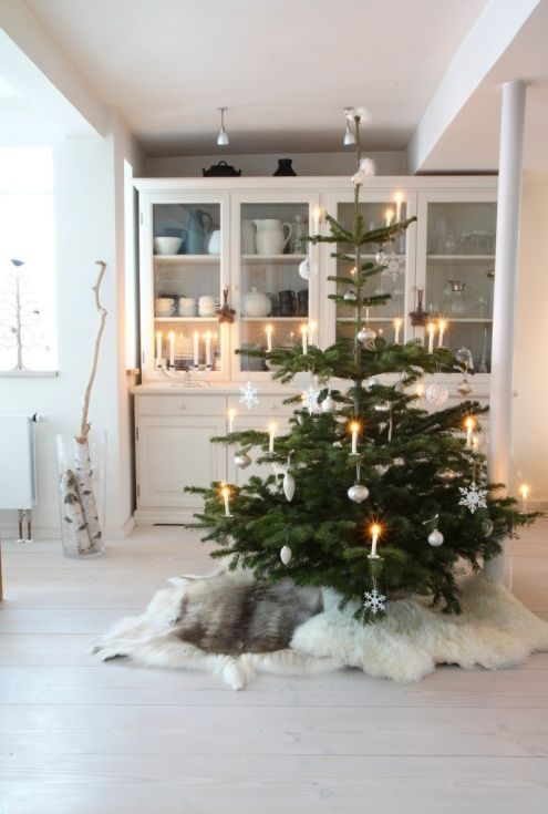 a Nordic Christmas tree with lights, snowflakes and ornaments, with white faux fur covers under the tree is very cozy