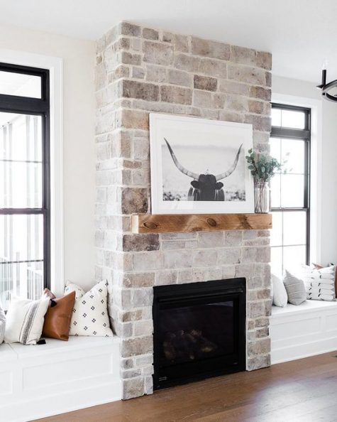 a neutral farmhouse living room with a whitewashed stone fireplace and a wooden mantel is very cool and welcoming