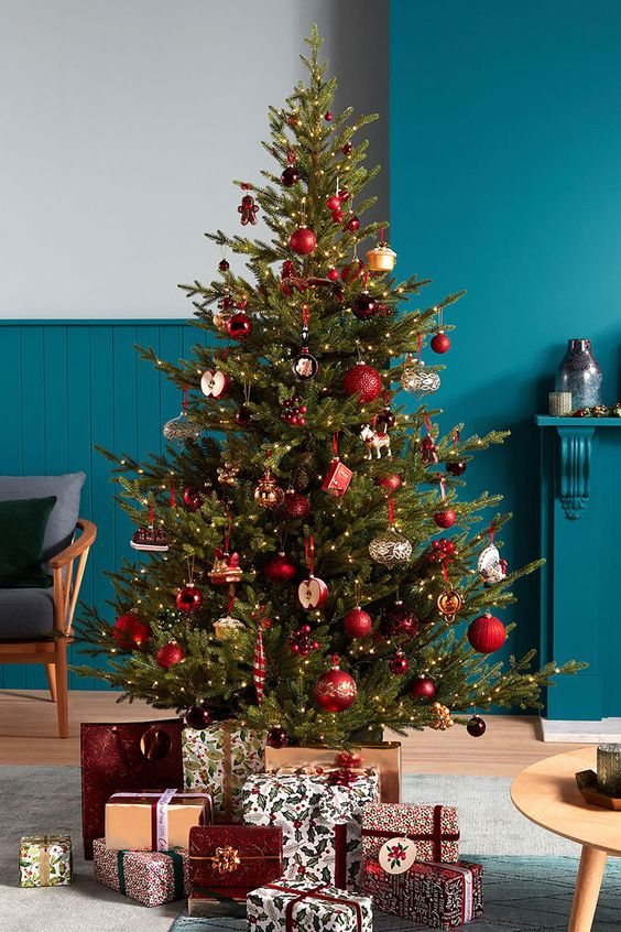 a green Christmas tree decorated with lovely red bauble ornaments and some whimsical like cupcakes and apples