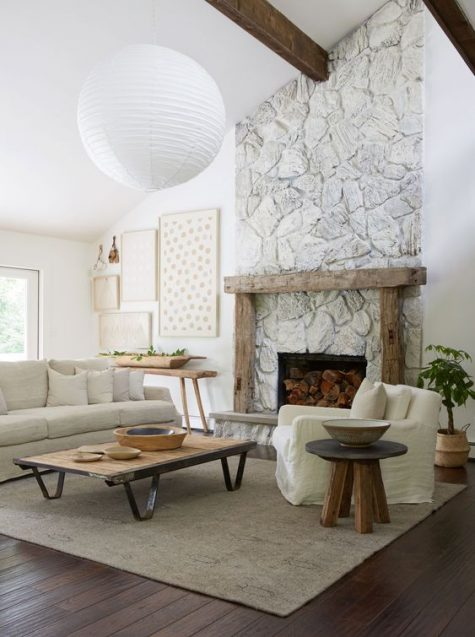 a neutral living room with a whitewashed stone fireplace, a wooden mantel and furniture, a gallery wall and a potted plant