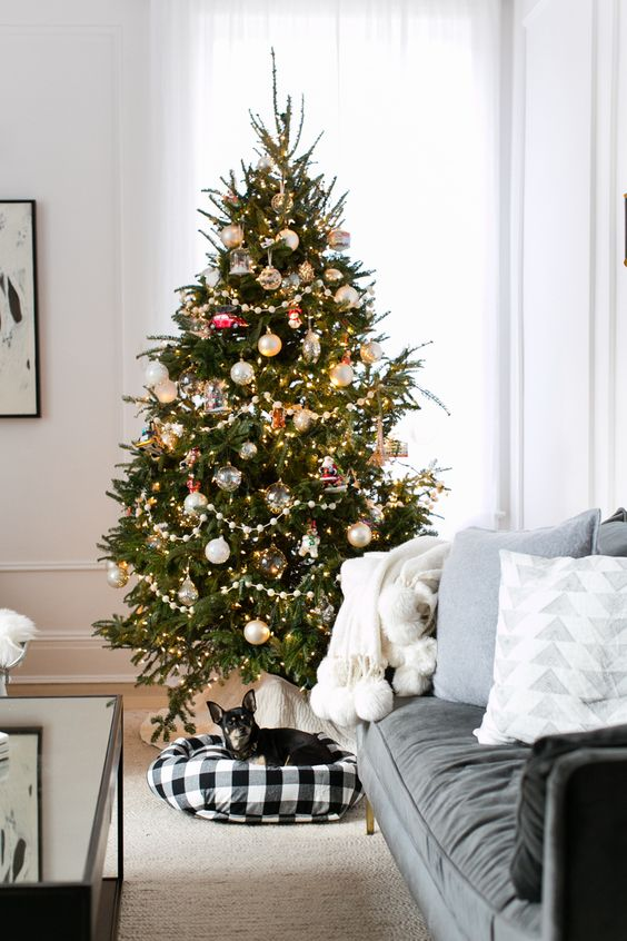 a plaid pet bed is a nice alternative to a usual Christmas tree cover or stand and your pet will be happy to stay there