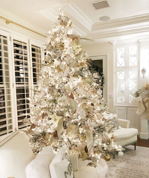 a winter wonderland Christmas tree - a flocked piece with white, silver and gold ornaments, fabric blooms and ribbons