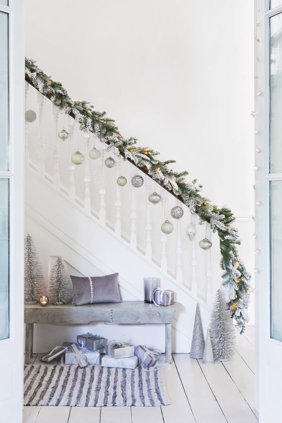 flocked fir branches with lights, pastel and silver ornaments hanging on the railing and silver and lavender decor