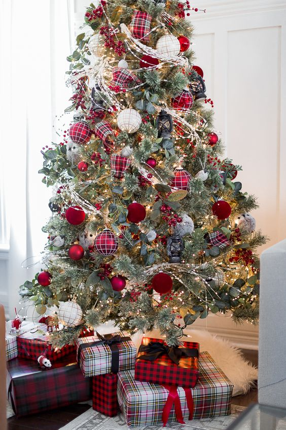 a lovely Christmas tree with lights, foliage, red and red plaid Christmas ornaments plus plaid gift boxes under the tree