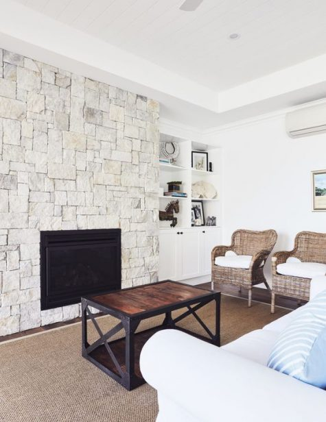 a neutral rustic living room with a whitewashed stone fireplace, wicker chairs and all neutrals