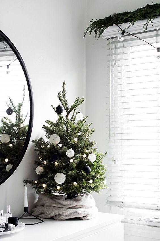 a pretty Scandinavian Christmas tree decorated with lights, white and black ornaments, with an old sweater covering the base