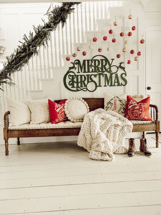 cozy Christmas stairs decor with gold and red ornaments hanging and green letters attached plus a lush fir branch garland