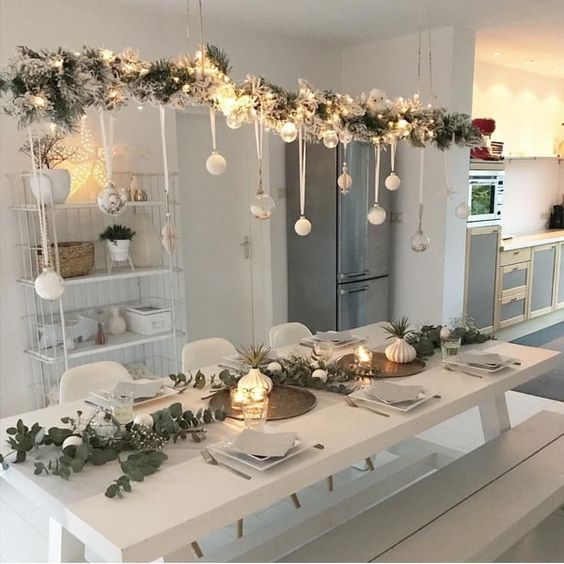 a beautiful overhead Christmas installation of flocked branches, lights, sheer and white ornaments is a pretty Nordic decor idea