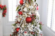 10 a lovely modern Christmas tree decorated with red and green ornaments, branches and berries, a wooden marquee light topper