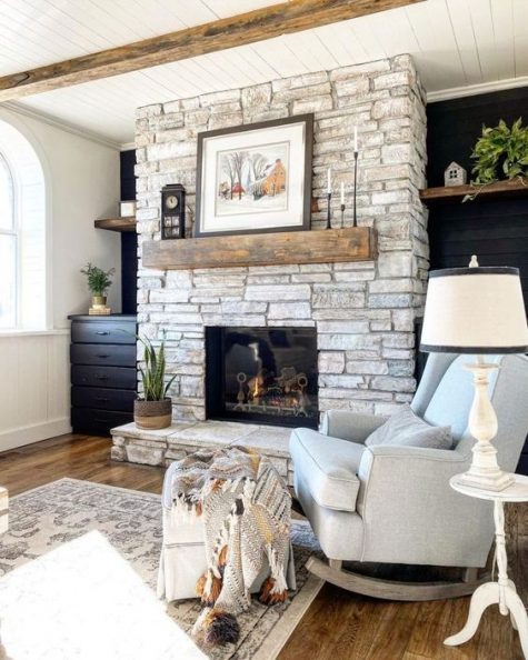a stylish farmhouse living room with a whitewashed stone fireplace, neutral and dark furniture and potted greenery