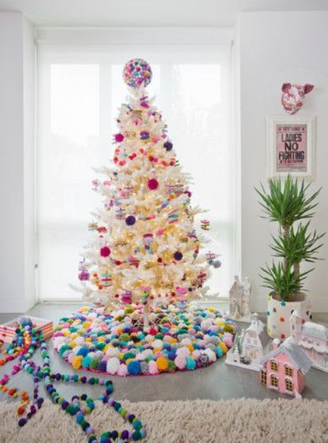 a white Christmas tree decorated with bold pompom ornaments and with a colorful pompom tree skirt and a ball on top