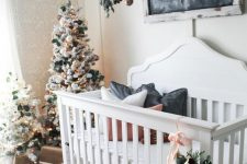 10 winter wonderland nursery decor with flocked Christmas trees decorated with white and hunter green ornaments and with an overhead installation with greenery and dark ornaments