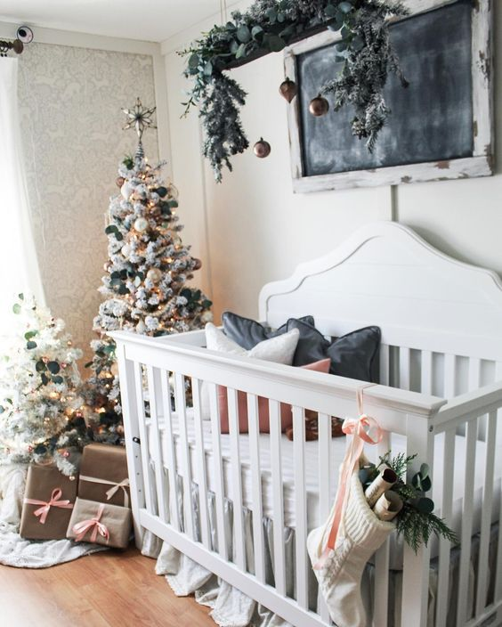 winter wonderland nursery decor with flocked Christmas trees decorated with white and hunter green ornaments and with an overhead installation with greenery and dark ornaments