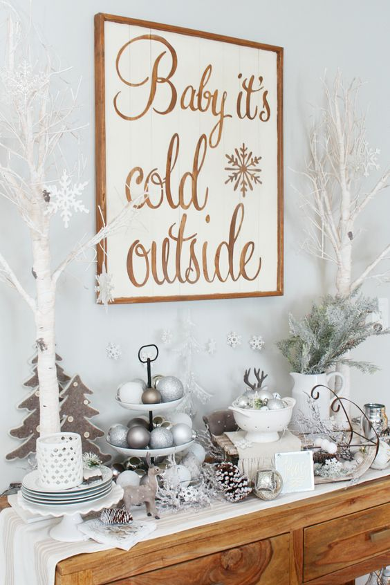 a bar idea for a winter wonderland space   a sign, some flocked Christmas branches, white trees, silver and white ornaments, candles and pompoms